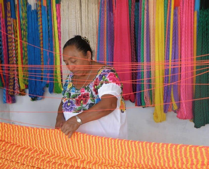 Mujer maya urdiendo hamacas